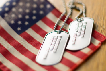 American flag with dog tags resting on top